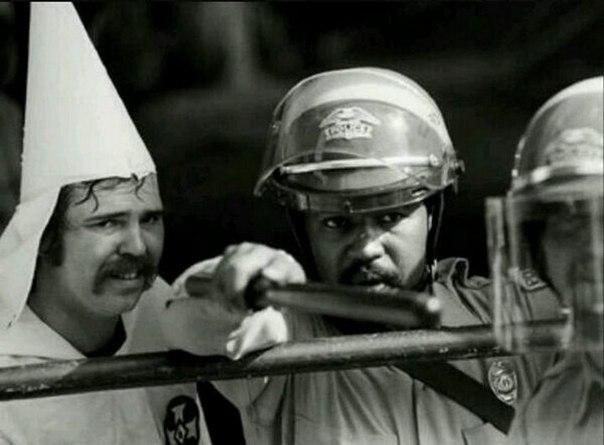 Черноволосый полицейский защищает членов Ку-Клукс-Клана